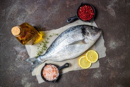 Fresh fish dorado and ingredients for cooking. Raw fish dorado with aromatic spices, herbs, lemon and vegetables. Sea bream fish cooking. Top view