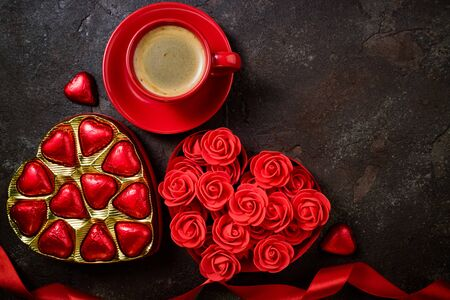 Valentines Day background with red heart, chocolate bonbons and coffee cup. Heart shape from ribbons and flowers rose. Happy Valentine Day