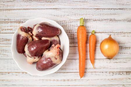 Raw turkey hearts with vegetables carrots and onion on white wooden background. Ingredients for cooking hearts offal. Healthy food concept 版權商用圖片