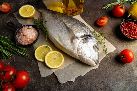 Raw fish dorado with lemon, herbs, spices and tomato on dark background. Healthy food and diet concept. Top view. Ingredients for cooking fish