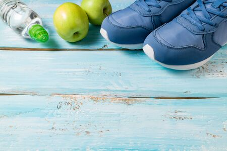 Sport shoes, apples, bottle of water on blue wooden background. Concept healthy lifestyle, healthy food, sport and dieting. Sport equipment. Copy space
