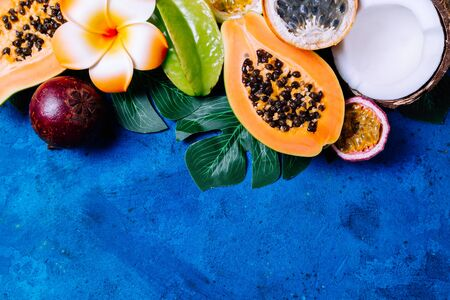 Summer tropical background with exotic various fruits, green palm leaves and flowers on blue. Fruits background. Top view, copy space