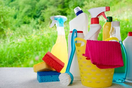 Basket with cleaning products on blurry spring background. Cleaning with supplies, cleaning service concept. Copy space