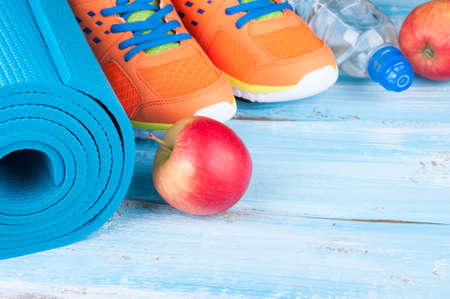 Yoga mat, sport shoes, apple, bottle of water on blue wooden background. Concept healthy lifestyle, healthy eating, sport and diet. Sport equipment. Selective focus