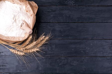 Baking background. Flour in paper bag and wheat on dark wooden table. Ingredients for cooking.  Top view. Copy space 免版税图像
