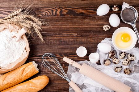Baking background. Ingredients for cooking. Flour in paper bag, eggs, butter and kitchen utensils on rustic wooden background. Cooking bread. Copy space. Top view 版權商用圖片