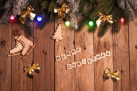 Christmas fir tree with decoration and christmas colorful lights on dark wooden background. Top view