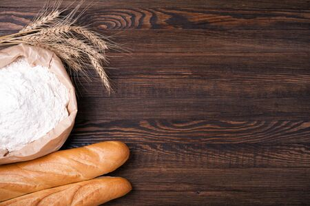 Flour in paper bag, wheat and baguette on wooden background. Baking background. Copy space. Top view Фото со стока