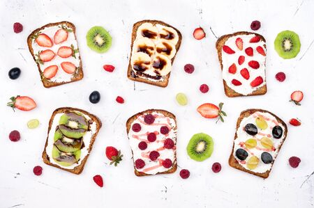 Healthy breakfast with toasts. Sweet sandwiches with cream cheese and fresh berries and fruit on white background. Top view