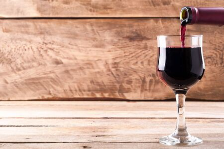 Red wine. Pouring red wine into wine glass on old wooden background. Copy space for your text