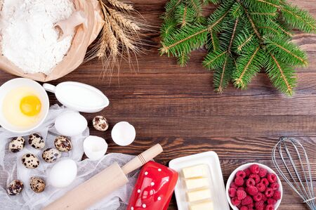 Baking background. Ingredients for cooking christmas baking - flour, eggs, butter, raspberries, milk, rolling pin and whisk on old wooden background. Christmas background. Top view. Copy space