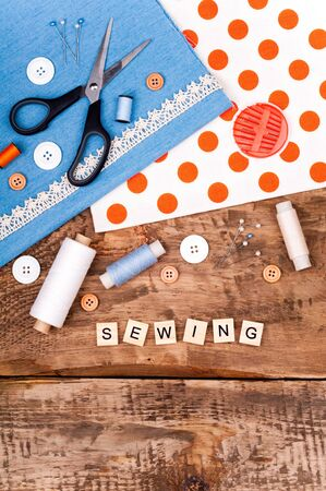 Sewing background. Fabric for sewing, lace and accessories for needlework on old wooden table. Spool of thread, scissors, buttons, sewing supplies. Set for needlework top view Stock fotó
