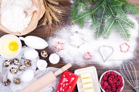 Baking background. Ingredients for cooking christmas baking - flour, eggs, butter, raspberries, milk, rolling pin and whisk on old wooden background. Christmas background. Top view