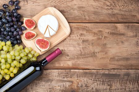 Bottle of red wine, grapes, cheese camambert and figs on old rustic wooden table. Food background. Top view. Copy space