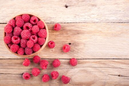 Ripe sweet raspberries in bowl on old wooden table. Copy space, top view