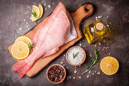 Fish raw snapper with lemon slices, herbs rosemary, salt and pepper on dark background. Healthy food and diet concept. Top view, copy space. Ingredients for cooking fish