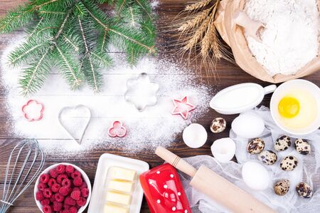 Ingredients for cooking christmas baking. Flour, eggs, butter, raspberries, milk, rolling pin, whisk and cookie cutters on old wooden background. Christmas background. Festive cooking. Top view