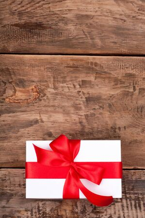 Christmas gift box on rustic wooden background. Holidays present. Copy space
