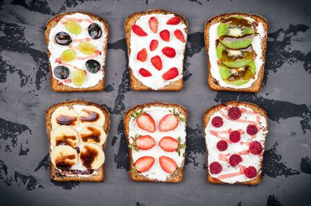 Healthy breakfast. Sweet sandwiches with cream cheese and fresh berries and fruit on dark background. Toasts for breakfast. Top view