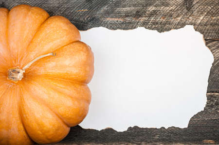 Pumpkin on old dark rustic wooden table. Halloween background with pumpkin and white blank of old paper. Autumn, halloween concept. Copy space, top view