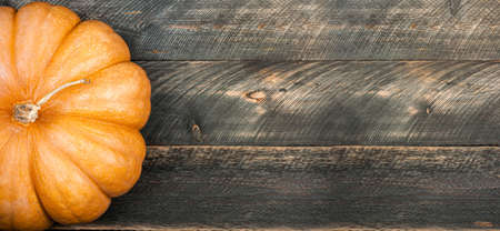 Pumpkin on dark rustic wooden table. Halloween background with pumpkin. Autumn, halloween, thanksgiving, holidays, autumn sale concept. Copy space long format for banner. Top view Banque d'images