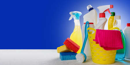 Variety house cleaning product on table with copy space. Basket with cleaning products on blue background. Cleaning service concept Banque d'images