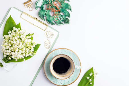 Home office desk table with coffee cup, bouquet of lilies of the valley flat lay. Workplace with notebook and decorations on white background. Blogging, freelance, feminine, florist concept. Top view Banque d'images