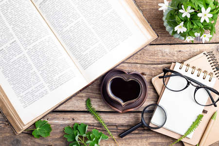Cup of coffee, open book, bouquet of flowers, pen, notebook, glasses and magnifier on old wooden background. Office desk table. Work, educations, reading concept. Top view