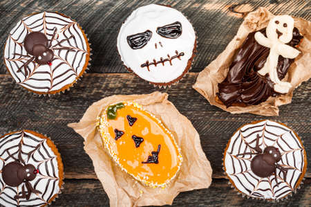 Funny delicious halloween cakes on old dark rustic wooden table. Halloween background with cakes for party. Autumn, halloween, party concept. Copy space, top view