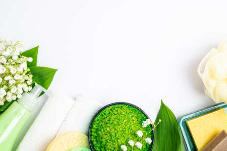 Spa treatment wellness concept. Natural spa cosmetics products, towels, accessories, bath sponge, soap, herbal sea salt, flowers on white background. Spa background flat lay. Copy space, top view Banque d'images