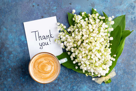 Notes thank you and coffee mug with bouquet of flowers lily of the valley on blue background. Thankfulness, coffee cup, customer service, thanks card concept, top view, flat lay