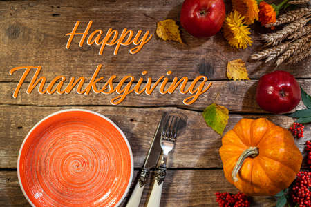 Thanksgiving background. Autumn table setting for Thanksgiving day party or Thanksgiving dinner. Plate, cutlery, pumpkin, floral, fruits and seasonal decoration on rustic wooden table