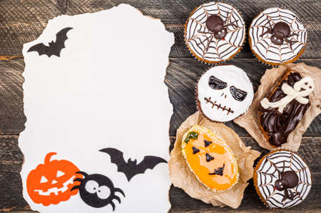 Halloween party cakes on old dark rustic wooden table. Halloween background with cakes. Autumn, halloween, party concept. Copy space, top view