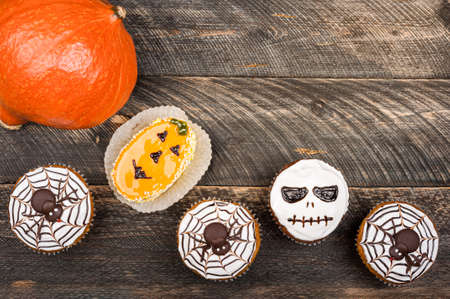 Pumpkin on old dark rustic wooden table. Halloween background with pumpkin and cakes. Autumn, halloween, party concept. Copy space, top view