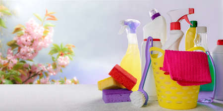 Basket with cleaning tools and products on blurry spring background. Spring cleaning, eco natural cleaning products concept. Copy space