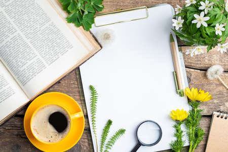 Open book, cup of coffee, bouquet of flowers, pen, notebook, white blank and magnifier on old wooden background. Office desk table. Work, studying, educations, reading, botanical concept. Top view, copy space