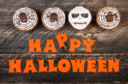 Funny delicious halloween pumpking cakes on old dark rustic wooden table. Halloween background with cakes for party. Autumn, halloween, party, card concept