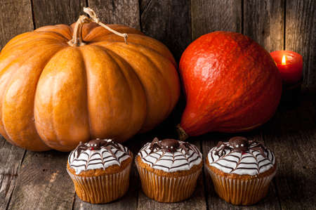 Pumpkins on old dark rustic wooden table. Halloween background with pumpkins and cakes. Autumn, halloween, party concept