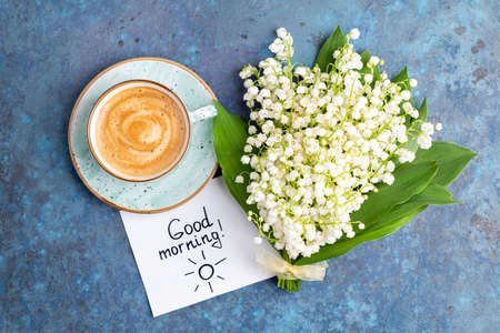 Notes good morning and coffee mug with bouquet of flowers lily of the valley on blue background. Breakfast, morning coffee, card concept, top view, flat lay