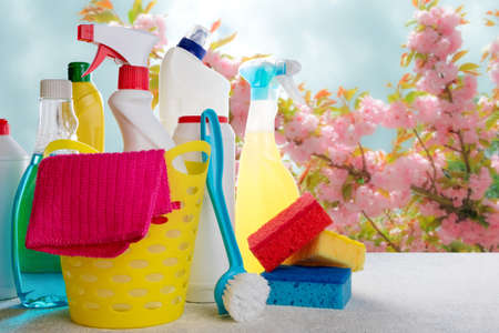 Basket with cleaning tools and products on blurry spring background. Spring cleaning concept