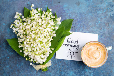 Notes good morning and coffee mug with bouquet of flowers lily of the valley on blue background. Breakfast, morning coffee, card concept, top view Banque d'images
