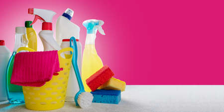 Variety house cleaning product on table with copy space. Basket with cleaning products on pink background. Cleaning service concept