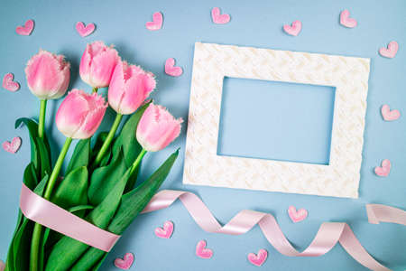 Bouquet of tulips flowers on blue. Spring flowers on floral pattern flat lay. Greeting card, holidays, spring concept. 8 March, Valentines background. Copy space