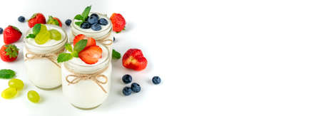 Fresh yogurt with berries in glass jars. Dairy products. Healthy food, dieting and breakfast concept. Long format for banner, copy space