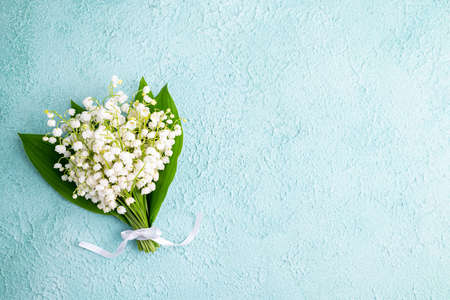 Bouquet of flowers lily of the valley on turquoise background flat lay, beautiful vintage card, top view. Spring, holidays, wedding concept. Copy space Banque d'images