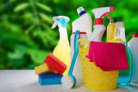 Basket with cleaning tools and products on blurry nature background. Spring cleaning, house, service, eco natural cleaning products concept