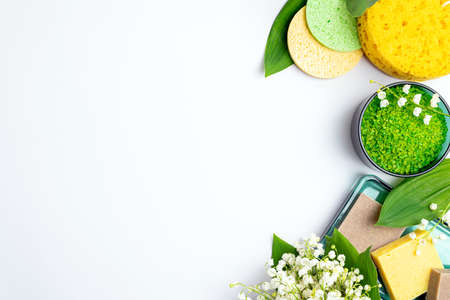 Spa treatment wellness concept. Natural spa cosmetics products, accessories, bath sponge, soap, herbal sea salt, flowers on white background. Spa background flat lay. Copy space, top view