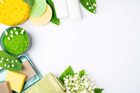 Spa treatment wellness concept. Natural spa cosmetics products, towels, accessories, bath sponge, soap, herbal sea salt, flowers on white background. Spa background. Copy space