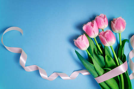 Floral pattern with spring flowers. Greeting card 8 March, Valentine's Day, happy birthday, Easter, holidays concept. Bouquet of tulips flowers on blue background. Copy space