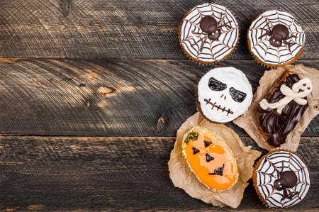Funny delicious halloween cakes on old dark rustic wooden table. Halloween background with cakesfor party. Autumn, halloween, party concept. Copy space, top view